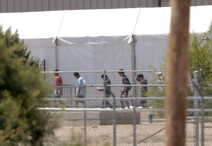 Detainees are seen outside tent shelters used to hold separated family members, Friday, June 22, in Fabens, Texas.