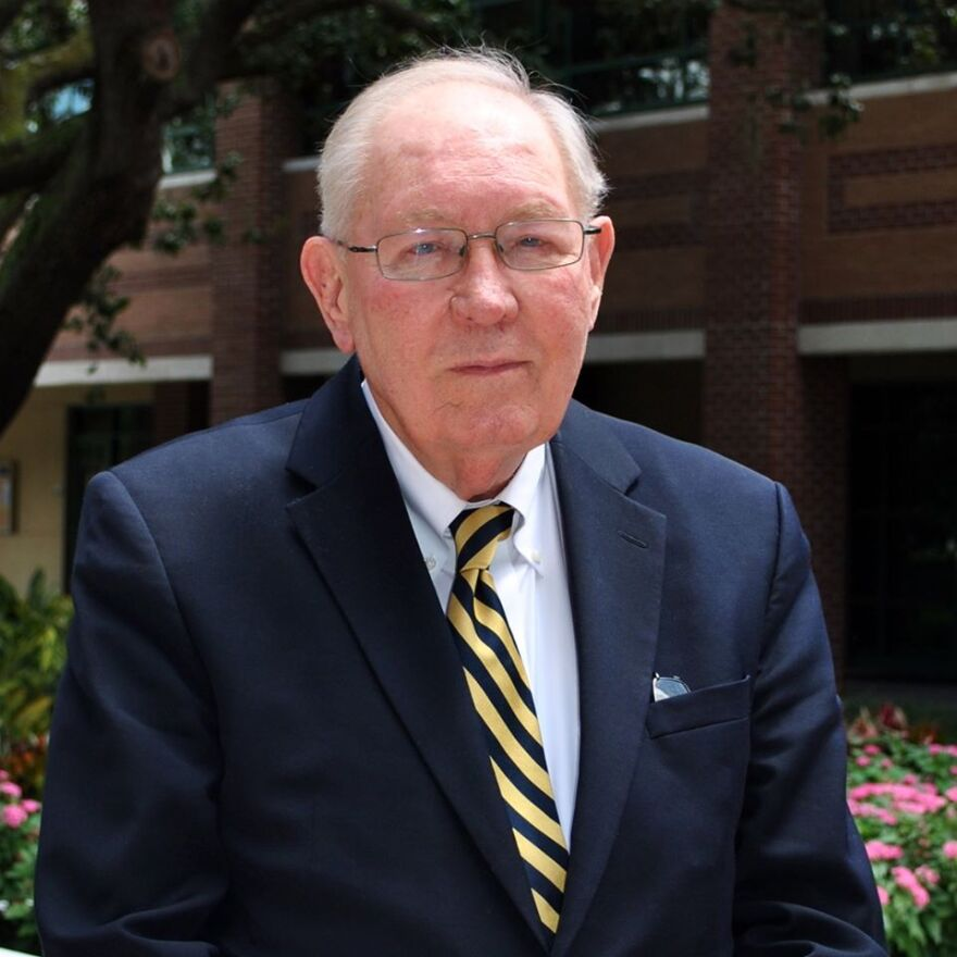 An elderly man in a blue suit with a striped tie and glasses