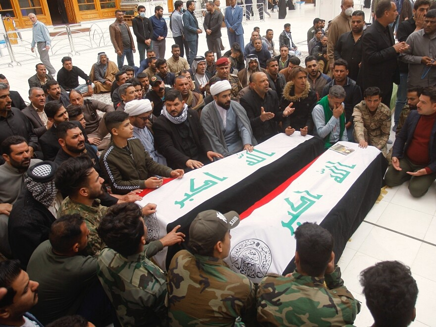 Mourners pray over the flag-draped coffins of two Popular Mobilization Forces fighters killed in the Thursday U.S. airstrike in Iraq, during their funeral procession at the Imam Ali shrine in Najaf, Iraq, Saturday.