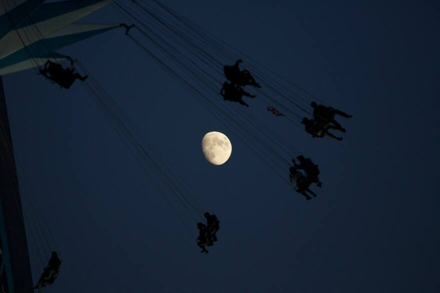 A waxing moon in the background of a fairground attraction in London on Sunday.