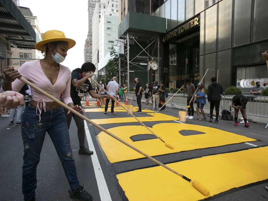 Azia Toussaint helps paint a Black Lives Matter mural on Fifth Avenue in front of Trump Tower on Thursday in New York.