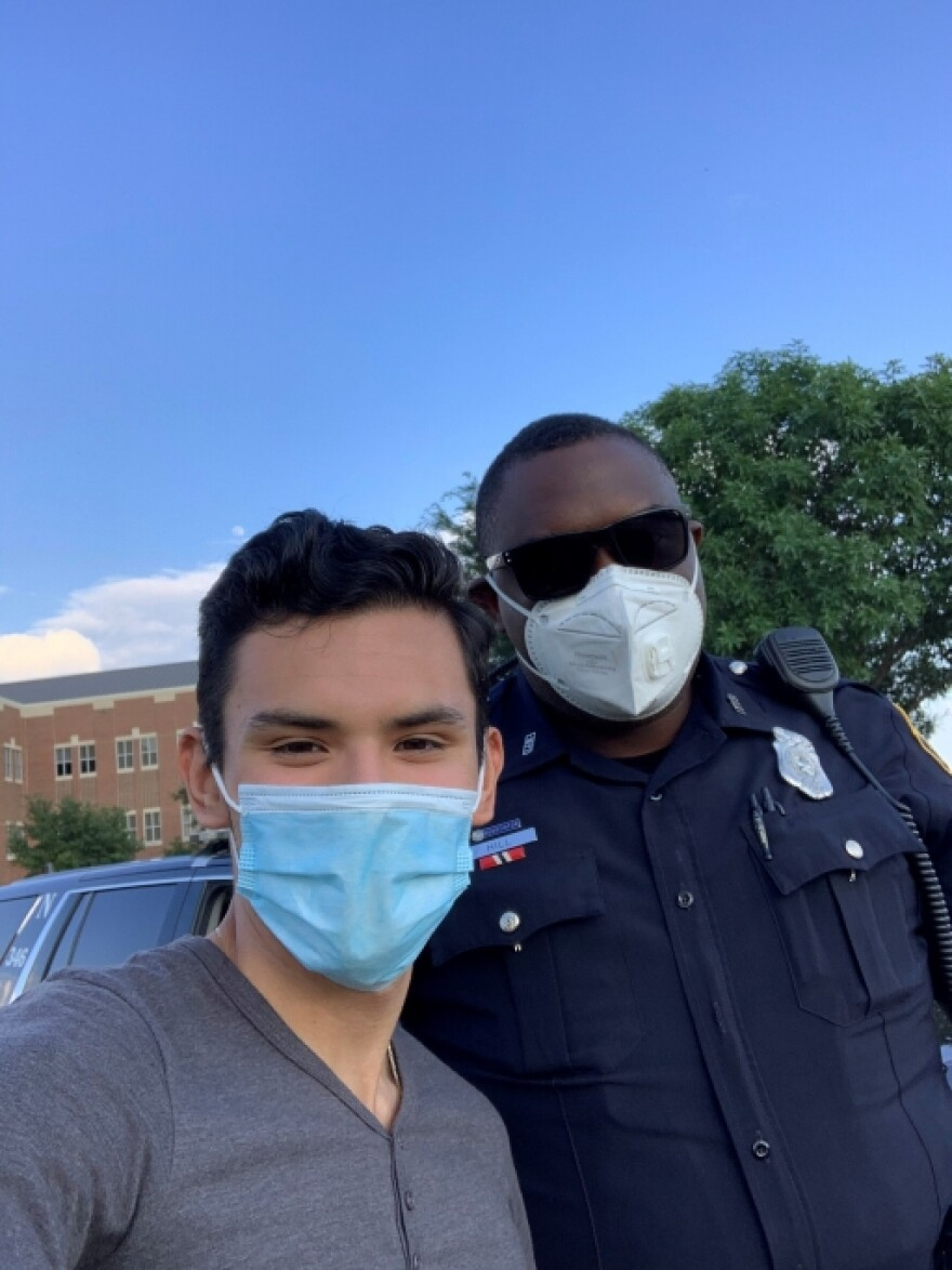 Izcan Ordaz, left, poses with a Fort Worth police officer at a recent Black Lives Matter protest near his high school.