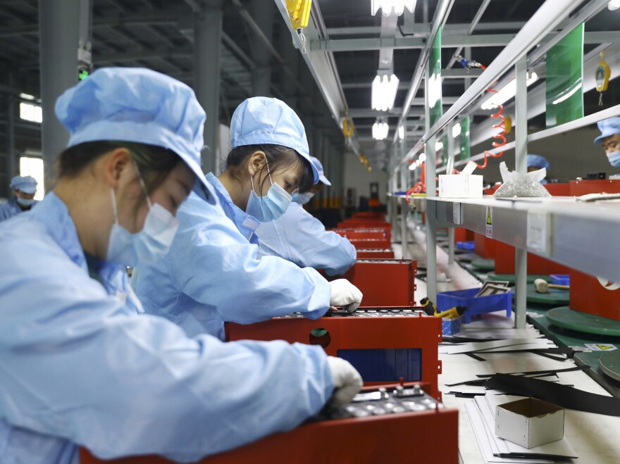 Employees work in the workshop of a lithium battery manufacturing company in Huaibei, eastern China, on Nov. 14. China posted a record trade surplus in November, led by a surge in exports to the United States.
