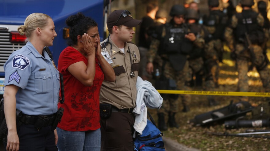 In shock: The scene outside a Minneapolis business Thursday. A gunman killed four people, wounded four others and then killed himself.