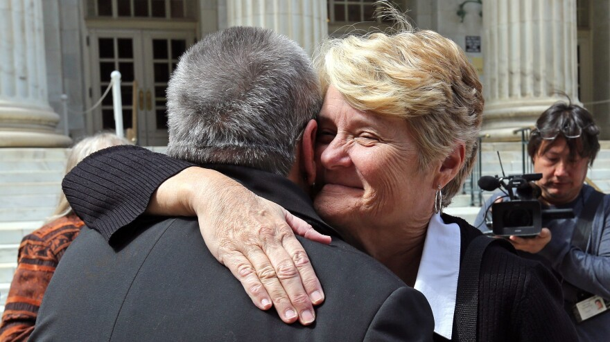 Sue Barton, a plaintiff challenging Oklahoma's gay-marriage ban, gets a hug from her pastor following a hearing at the 10th U.S. Circuit Court of Appeals in Denver on April 17