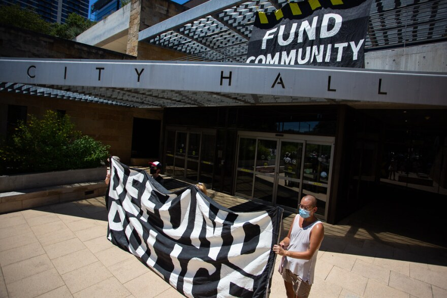 Protesters call for the defunding of the Austin Police Department outside City Hall on July 11.