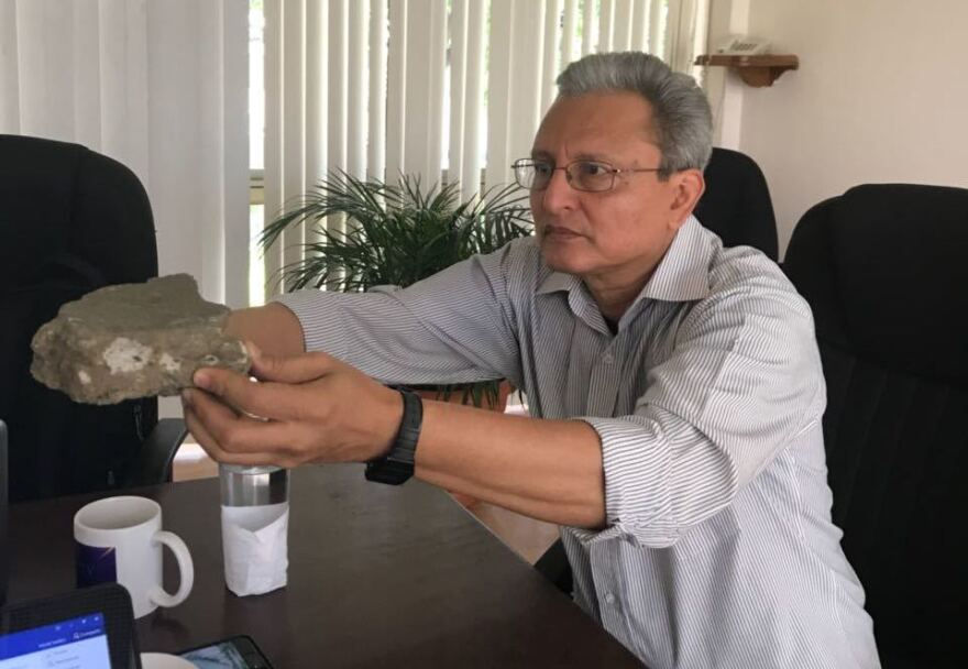 Chepe Idiáquez holds up a rock he says was thrown at him by a mob of pro-government supporters. He keeps the rock on his desk as a symbol of Nicaragua's political violence.