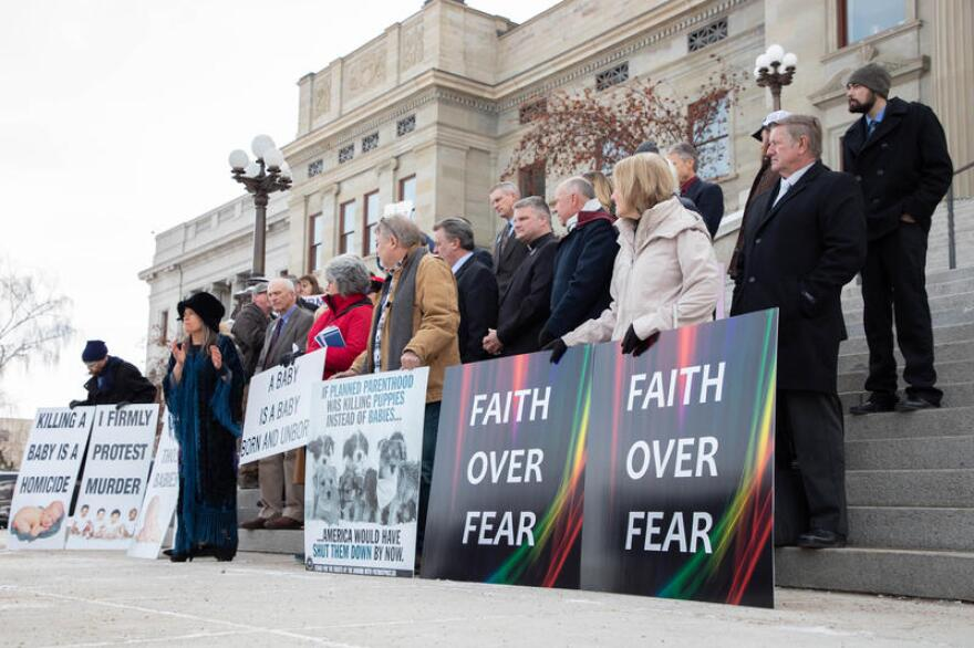 """People stand on the Montana Capitol steps with signs that read """"Faith Over Fear."""""""
