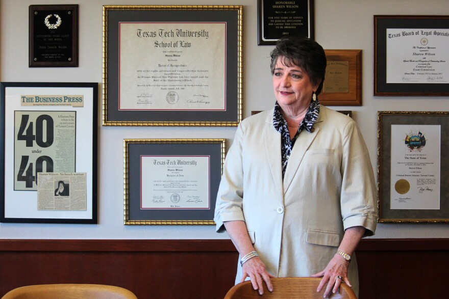 Tarrant County District Attorney Sharen Wilson stands in front of a wall full fo framed diplomas, certificates and press clippings in her office in 2019.