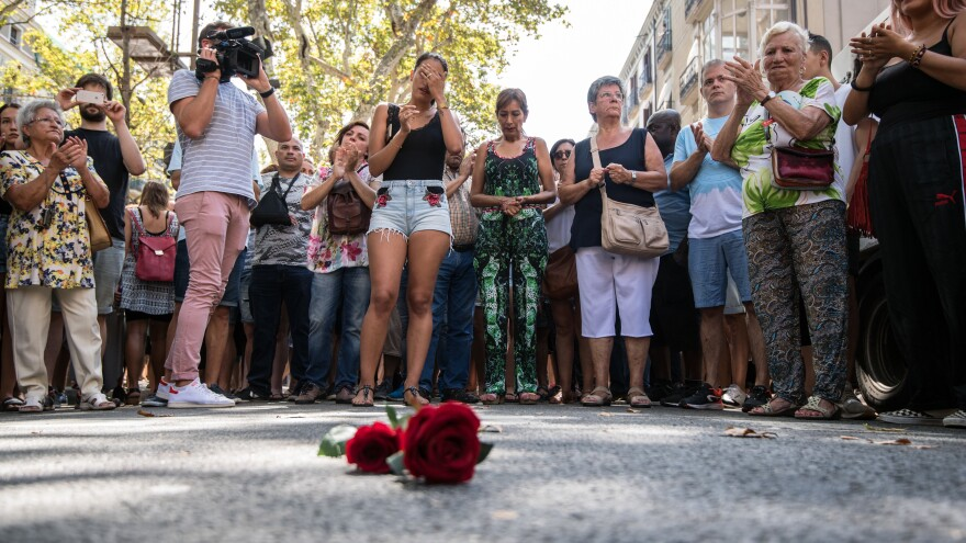 People gather around a single rose laid on the ground of Las Ramblas in Barcelona on Friday, observing one minute's silence for the victims of the terrorist attack.