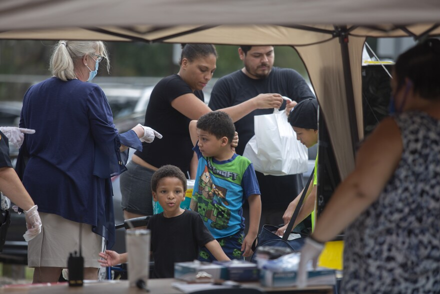 A family picks up bags of food from a canvas pop up tent in front of a school.