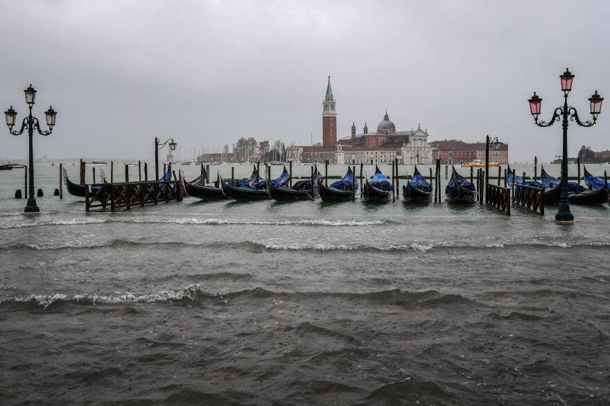 Gondolas are moored by the flooded Riva degli Schiavoni waterfront in Venice.