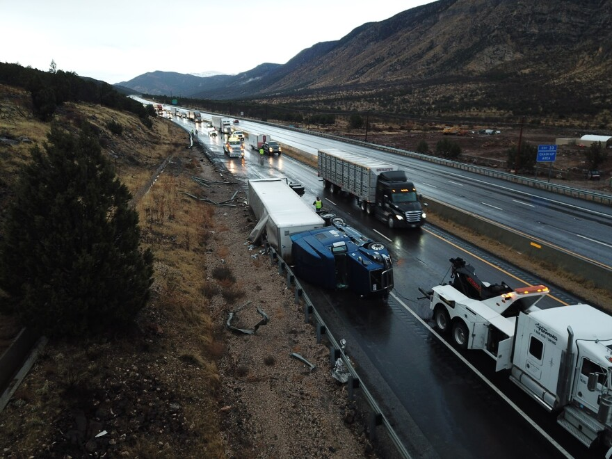 A semitrailer lays on its side as traffic piles up behind it.