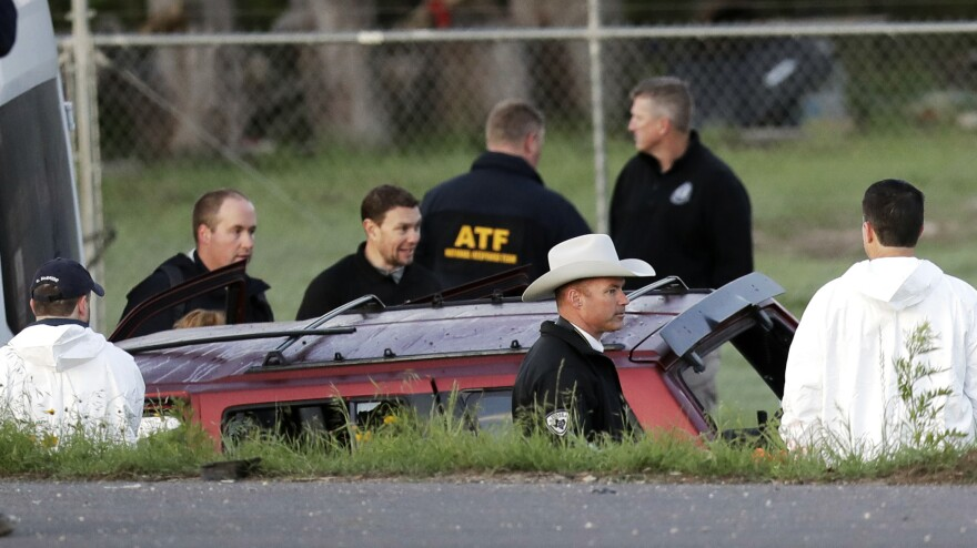 Officials investigate the scene where suspect Mark Anthony Conditt died in an explosion early Wednesday. His red vehicle was trapped between two white vans in Round Rock, Texas.