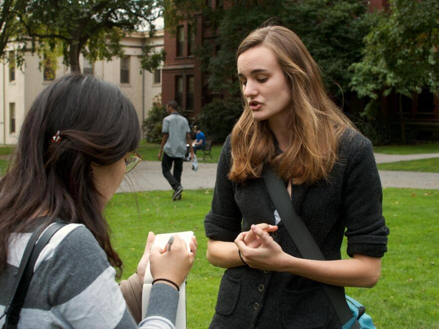 """Brown University senior Emily Kirkland (right) speaks with a student newspaper reporter. Kirkland, who studies environmental science, has been leading a divestment campaign at Brown and says she has seen how powerful such protests can be. """"Our administration is taking us very seriously,"""" she says."""