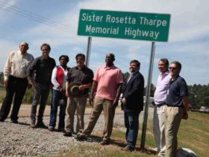 Arkansongs host Stephen Koch (with hat) is flanked by Cotton Plant Historical Museum Director Angela Ryland and Mayor Willard C. Ryland Sept. 29 at the unveiling of a sign dedicating part of state Highway 17 in honor of Sister Rosetta Tharpe, eight miles southeast of Cotton Plant.
