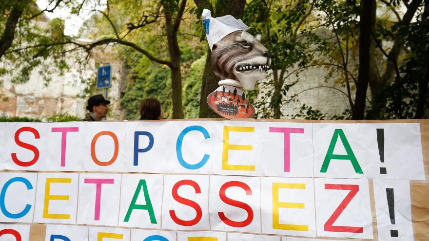 """A banner reads """"Stop CETA - it's enough"""" during a protest in front the Walloon parliament in Namur, Belgium, during a meeting on the EU-Canada Comprehensive Economic and Trade Agreement."""