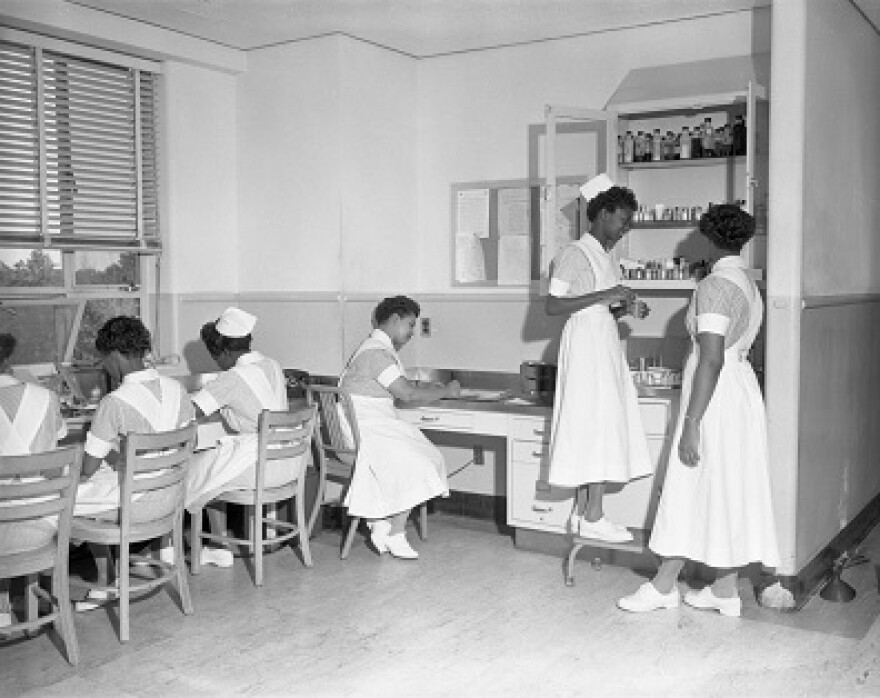 Nurses in uniforms are sitting and standing around inside the FAMU hospital in 1953