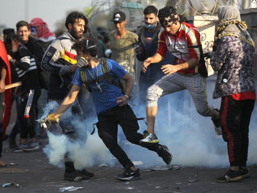 An Iraqi protester grabs a tear gas canister fired by riot police amid clashes following a demonstration east of Tahrir Square, on Monday.