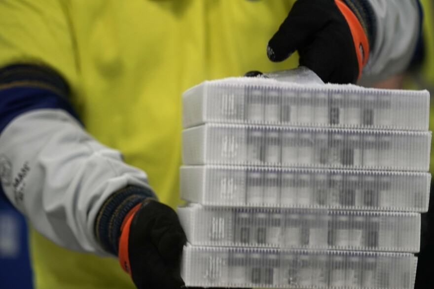 A worker carries boxes containing the Pfizer-BioNTech COVID-19 vaccine that were being prepared for shipment from a Pfizer facility in Portage, Mich., in December.