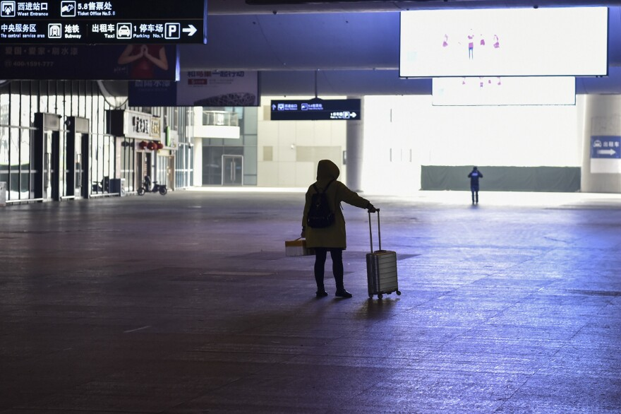 A passenger stands after arriving at the nearly-deserted Wuhan train station, usually full of passengers ahead of the Lunar New Year in Wuhan, China on January 23, 2020.
