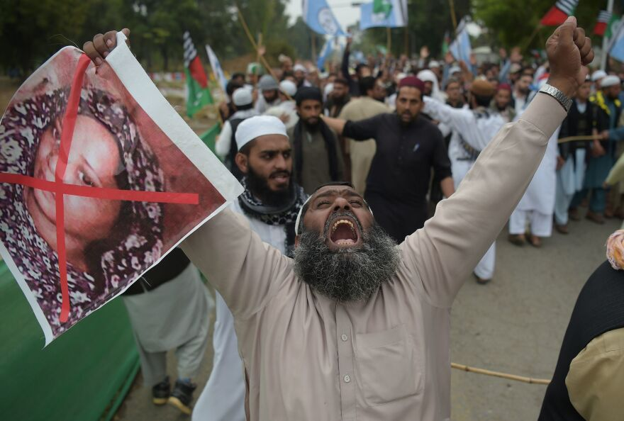 A Pakistani supporter of the Ahle Sunnat Wal Jamaat (ASWJ), a hardline religious party, holds an image of Christian woman Asia Bibi during a protest rally following the Supreme Court's decision to acquit Bibi of blasphemy in Islamabad.