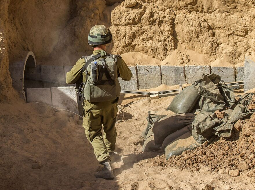 An Israeli army officer walks near the entrance of a tunnel allegedly used by Palestinian militants for cross-border attacks this past summer, at the Israel-Gaza border. Construction of such tunnels is what has led Israel to strictly regulate the importation of cement into Gaza.