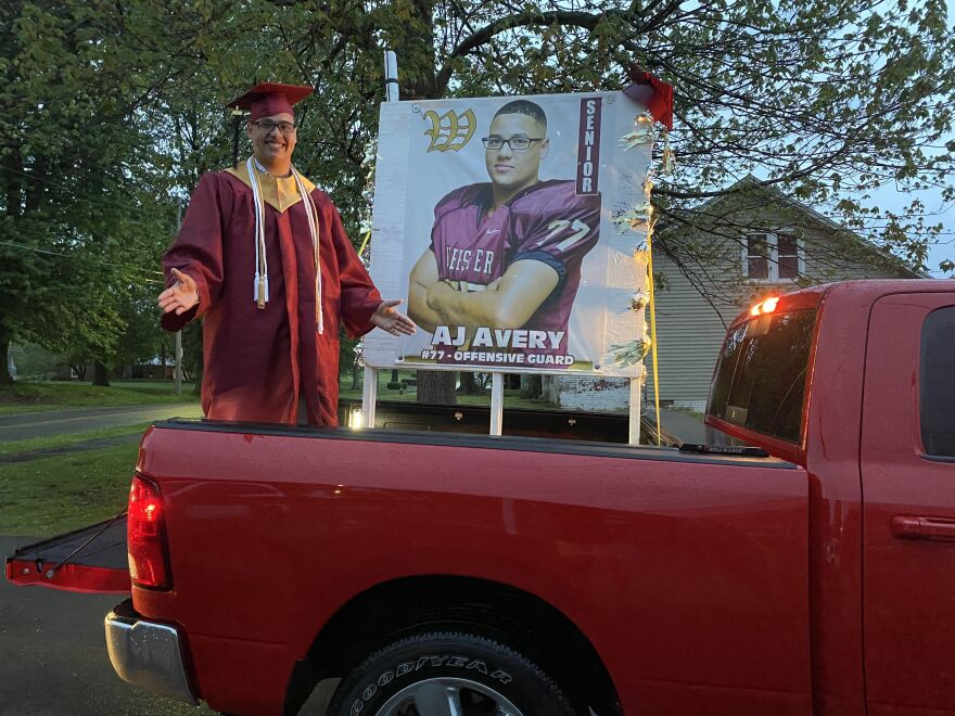 Ali Avery Jr., who goes by A.J., stands in the back of his family's pickup truck in the driveway of his home. His family decorated their vehicle for the drive-through ceremony.