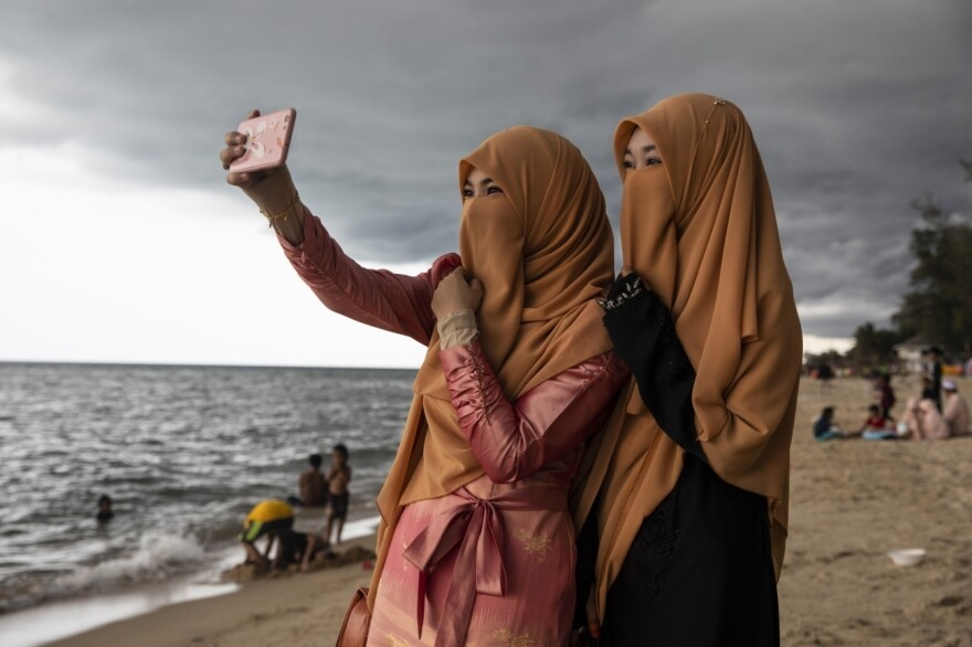 Women take a selfie on the Moslem holiday of Eid al-Fitr on Thailand's Talo Kapo beach.