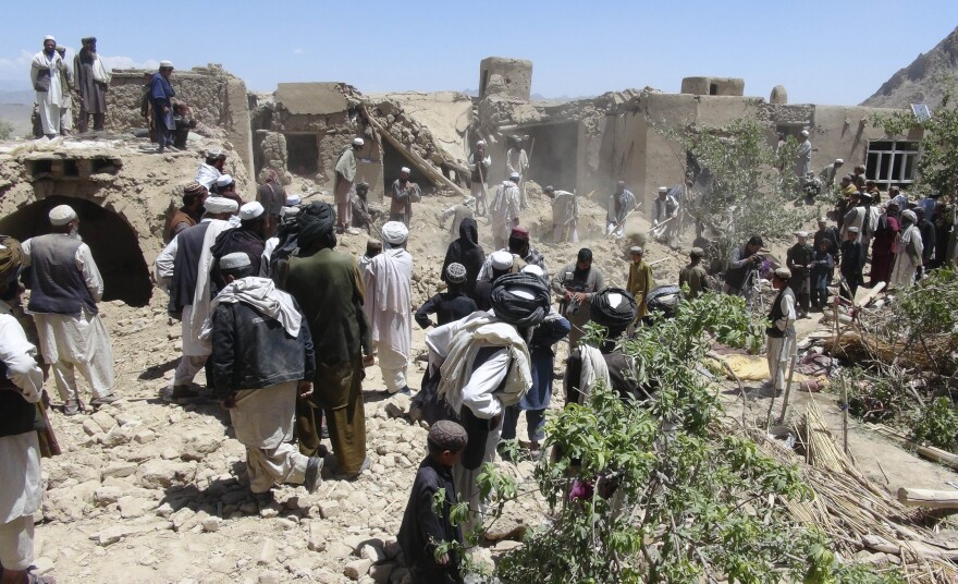 In this Wednesday, June 6, 2012 file photo, Afghan villagers gather near a house destroyed in an apparent NATO raid in Logar province, south of Kabul, Afghanistan.