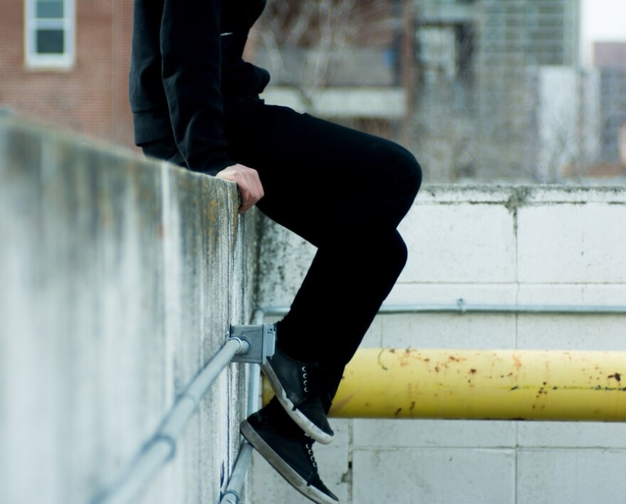 A boy in black sitting on a ledge with his legs hanging down