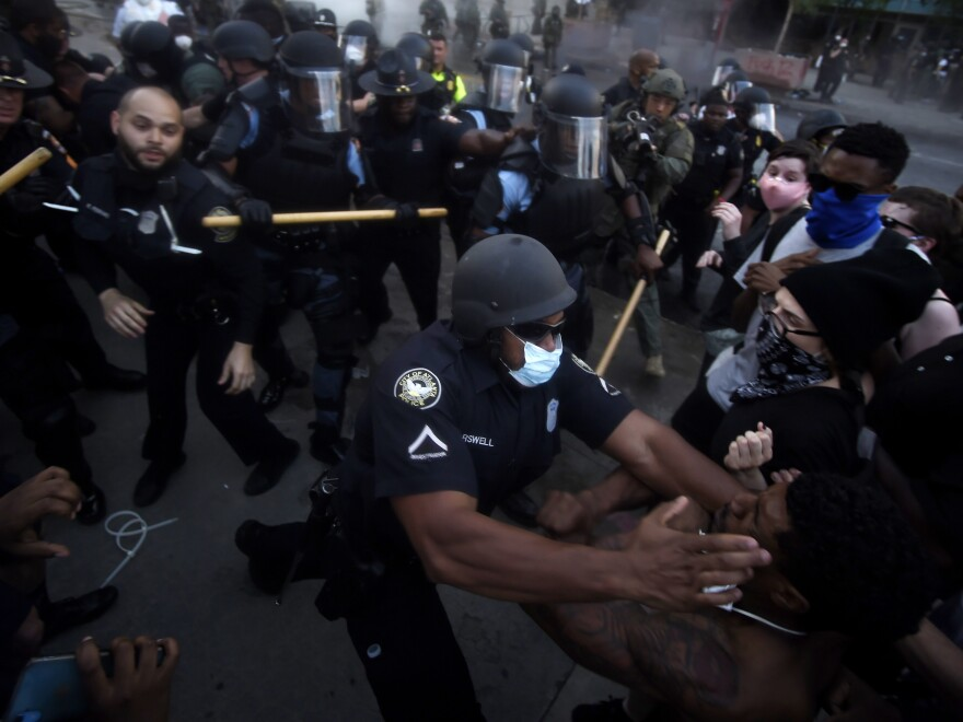 Police officers and protesters clash on Friday near CNN Center in Atlanta, in response to George Floyd's death in police custody in Minneapolis on Memorial Day.