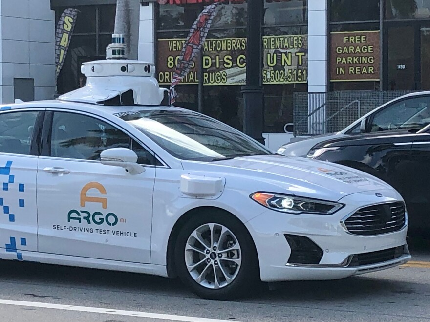 A Ford Fusion outfitted with Argo AI autonomous vehicle technology driving along Biscayne Blvd. near downtown Miami.
