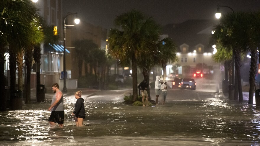 Hurricane Isaias made landfall near Ocean Isle Beach, N.C., near the border with South Carolina. Pictured are people walking through floodwaters in Myrtle Beach, S.C.