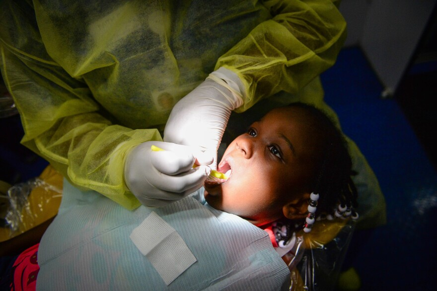 Michelle Shoates, 5, has her teeth cleaned by dental hygienist Faith Carnes on the dental bus.