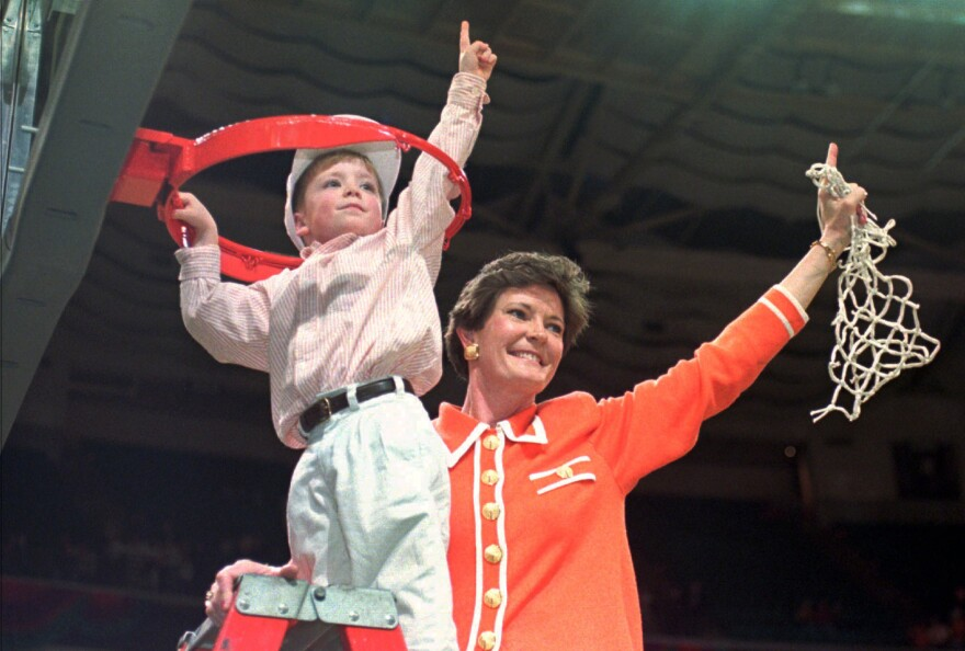 Tennessee coach Pat Summitt and son Tyler, 5, take down the net after the Lady Vols won the NCAA women's Division I title in Charlotte, N.C, on March 31, 1996.