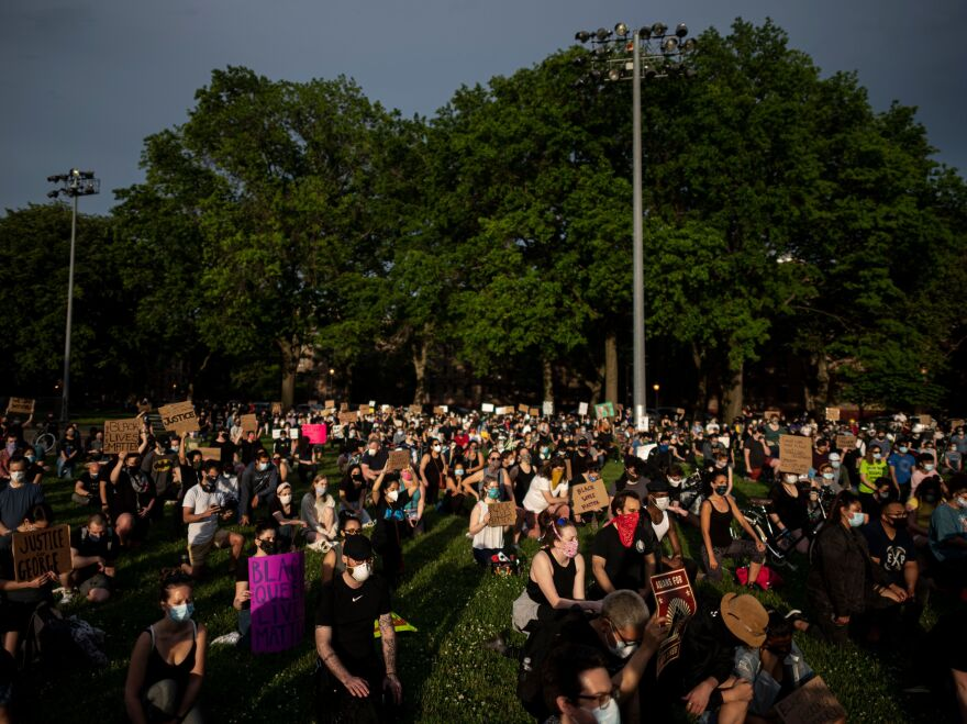 """Protesters kneel down and hold placards as they take part in a """"Black Lives Matter"""" vigil Wednesday in the Queens borough of New York City."""