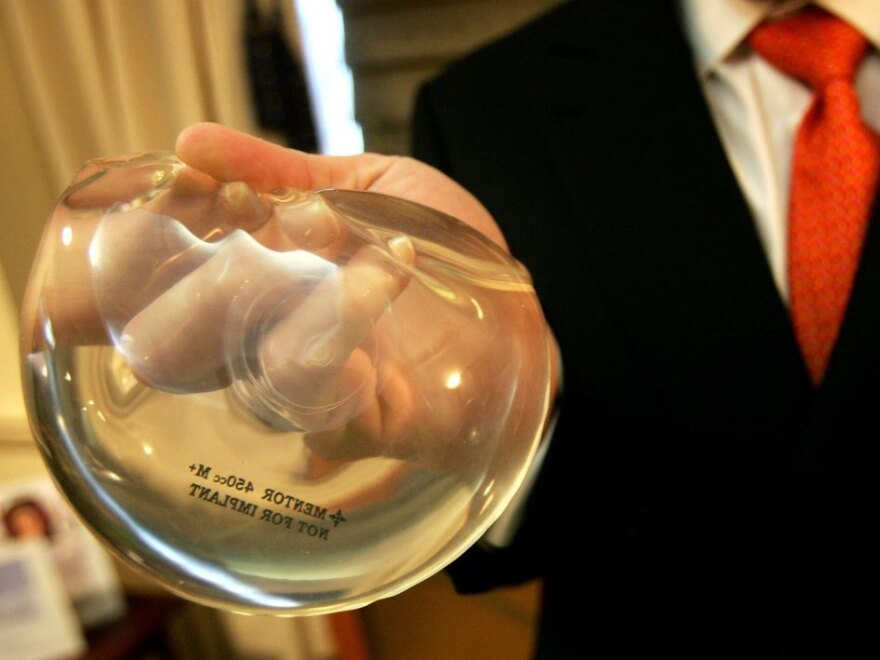New York plastic surgeon Brad Jacobs holds a silicone gel breast implant in 2006. That year the FDA allowed silicone implants back on the market, after a 14- year hiatus.