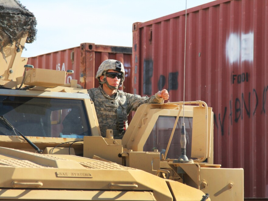 A driver of an armored vehicle  waits for fuel. More than 30,000 troops have passed through the Kalsu base as the U.S. shutters its military bases in Iraq.
