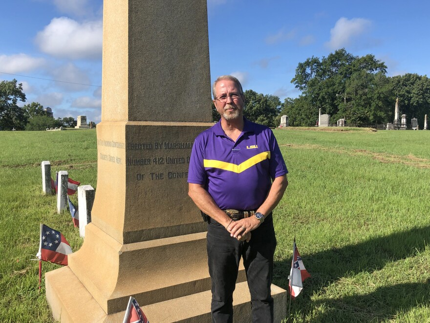 Bill Elliott, local commander of the Sons of Confederate Veterans, stands before an obelisk honoring unknown Confederate soldiers buried in the city cemetery. Some locals suggest the soldier statue should be moved to the cemetery.