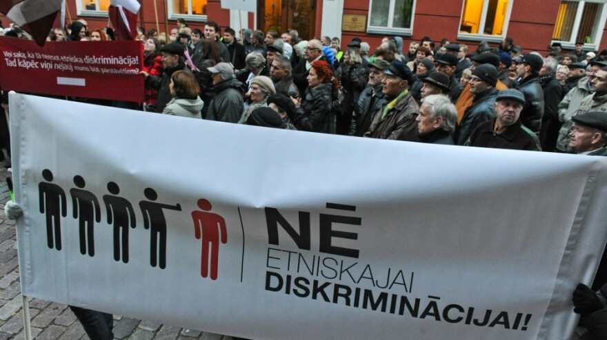 """In September, the pro-Russia Harmony Center party won parliamentary elections in Latvia. But the governing coalition has left the party on the sidelines. Supporters of the Harmony Center party protest in front of the Parliament building during its opening session in Riga on Oct. 17. The banner reads: """"No to ethnic discrimination."""""""