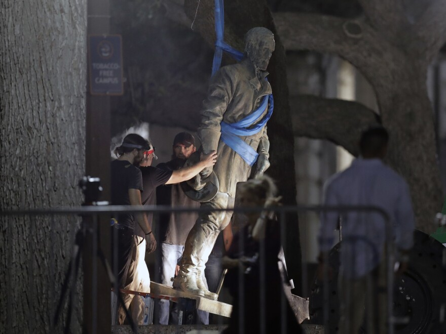 A statue of Confederate Gen. Robert E. Lee is removed from the University of Texas campus early Monday morning in Austin. University President Greg Fenves ordered the immediate removal of the Lee statue and three other prominent Confederate-era figures following recent violence in Charlottesville.