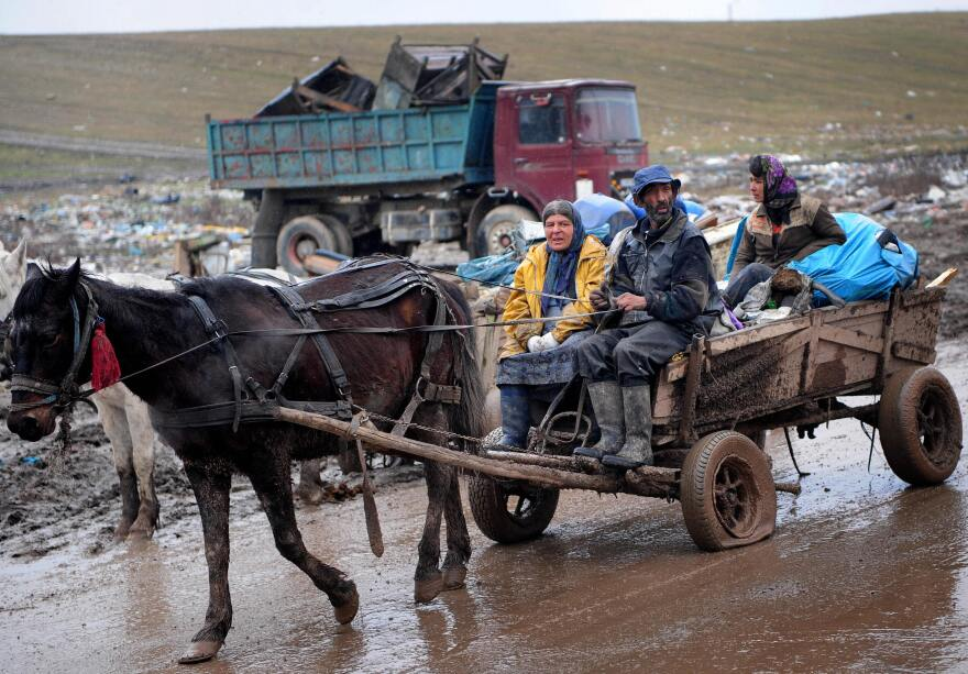 A Roma family rides a horse-drawn cart carrying scrap metal out of Romania's Pata-Rât city dump.