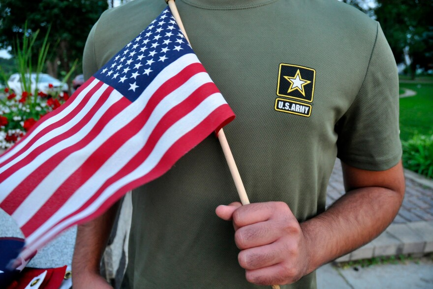 A Pakistani recruit, 22, who was recently discharged from the U.S. Army, holds an American flag as he poses for a picture. The U.S. Army has stopped discharging immigrant recruits who enlisted seeking a path to citizenship, at least temporarily.