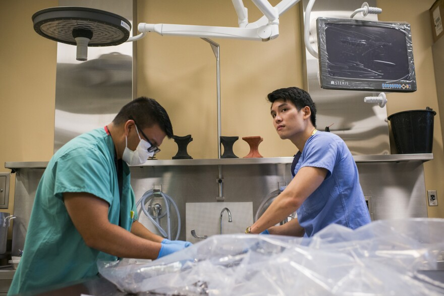 Forensic Anthropologists Kalani Carreira and Matthew Go process Korean War remains in the autopsy room at the DPAA.