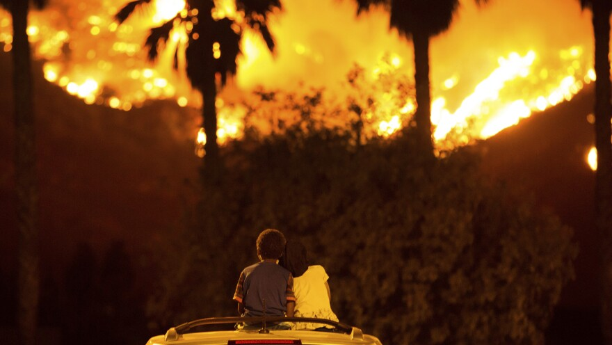 King Bass sits and watches the Holy Fire burn from on top of his parents' car as his sister, Princess, rests her head on his shoulder last week in Lake Elsinore, Calif. More than a thousand firefighters battled to keep a raging Southern California forest fire from reaching foothill neighborhoods.