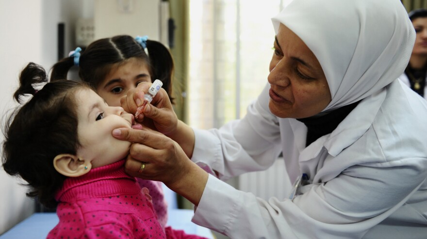 A health worker administers polio vaccine as part of a UNICEF-supported campaign in Damascus. Aid agencies sometimes have to negotiate with rebel groups and work in dangerous situations to immunize vulnerable children.
