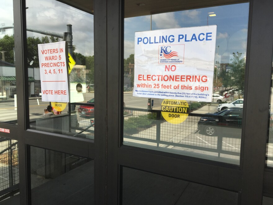 Automatic glass doors with placards announcing location is a polling place and no electioneering within 25 feet.