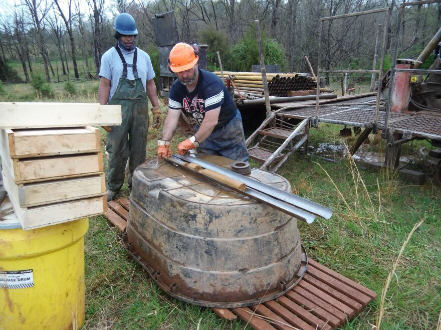 Workers pull core samples out of the drill.