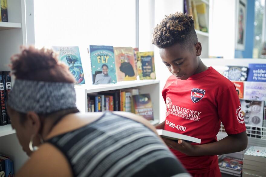 Brandon Wooten, 11, picks out books for summer reading at EyeSee Me.